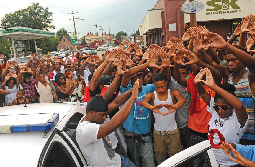 At a 2013 vigil for Garrick Ellis in Highland Springs, friends holds their hands high, thumbs and forefingers touching in a tribute to their murdered friend's basketball skills. Ellis was shot on the city's North Side at the age of 18 — almost two decades earlier, his father also died by gunshot in Church Hill. - SCOTT ELMQUIST