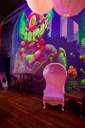 Alice in Wonderland-inspired decor includes a mural of the Cheshire Cat and whimsical furniture. - TYLER DARDEN