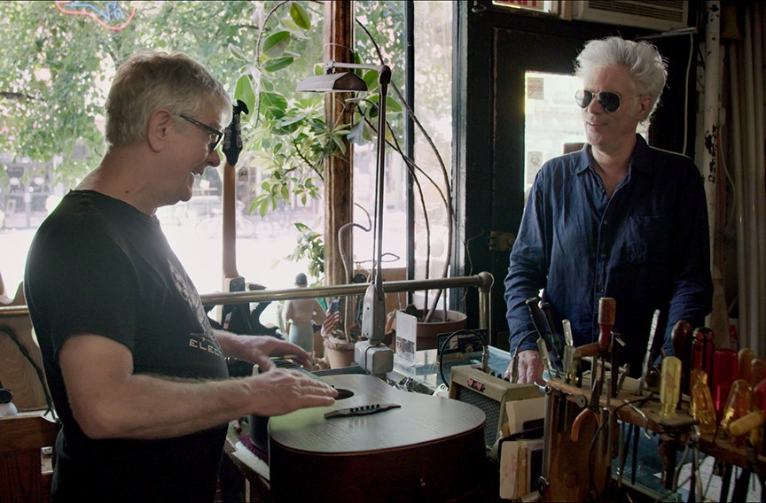 """Rick Kelly talks to one of his guitar customers, famous indie film director Jim Jarmusch in """"Carmine Street Guitars."""" Jarmusch gave Mann the idea to make a documentary about the shop."""