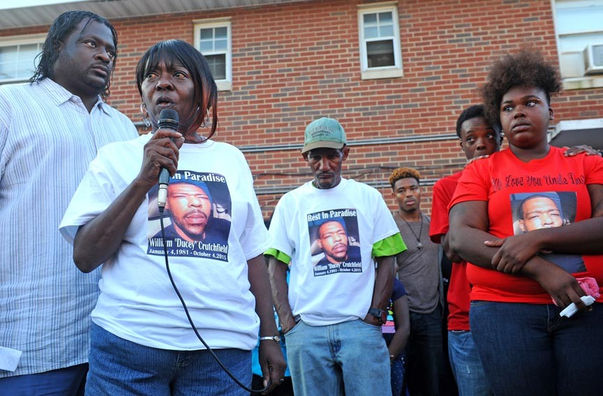 """Darlene Crutchfield speaks during a vigil following the fatal shooting of her son William """"Ducey"""" Crutchfield in Mosby Court, with his father at center. Crutchfield was one of six homicide victims in the public housing complex this year. - SCOTT ELMQUIST"""