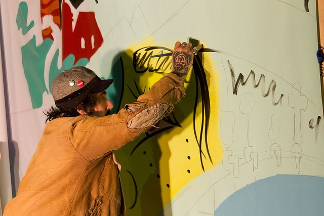 Mickael Broth works in the wind and cold on his portable mural outside of Casa del Barco.