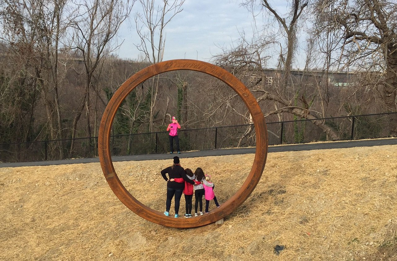 People take a photo inside one of artist Josh Wiener's rings, part of Richmond's latest public art installment at the south entrance of the T. Tyler Potterfield Memorial Bridge. - SCOTT ELMQUIST