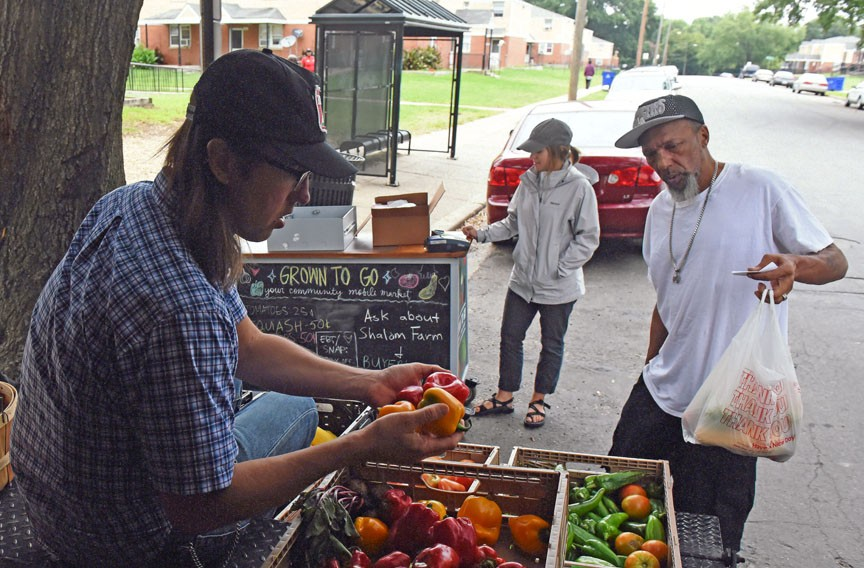Robert Nixon buys a bag of squash from volunteer Chad Kingstrom at one of Shalom Farms' mobile distribution markets in Creighton Court. The pop-ups travel to 10 locations around Richmond on a weekly basis throughout the growing season. - SCOTT ELMQUIST