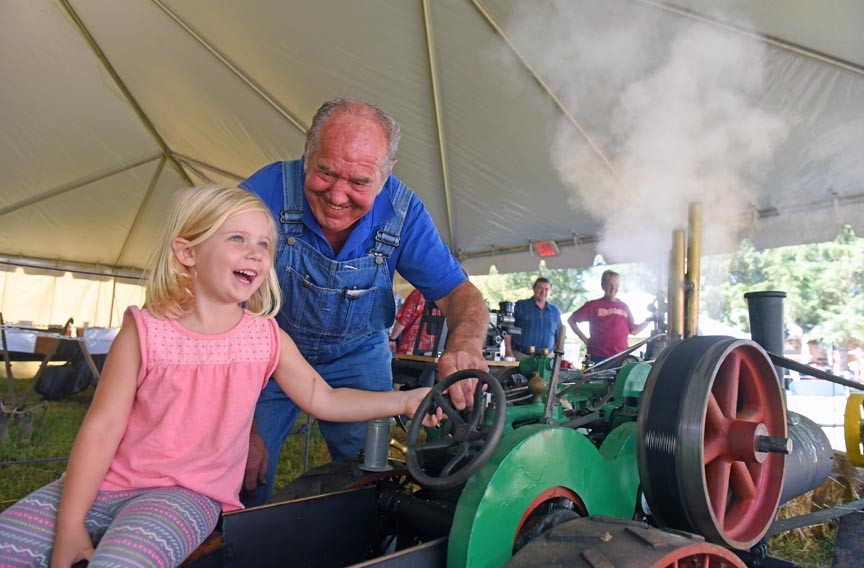 John Soderberg of Virginia Beach lets Elise Flynn blow the steam whistle on a one-third-scale replica of a 1915 steam traction tractor. - SCOTT ELMQUIST