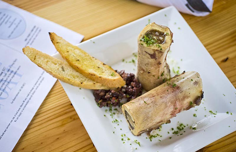 Veal marrow bone is seasoned with gray sea salt and served with tapenade bruschetta at the Blue Goat. - ASH DANIEL