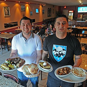 Vedran Oklopcic and Emir Vejzovic can't contain their enthusiasm for the food they're serving at Balkan Restaurant on Patterson Avenue. They're showing the Balkan mixed platter with grilled beef, chicken, beef sausage, cevapi and pljeskavica; lepinja bread, stuffed sour cabbage and Hungarian goulash with mashed potatoes. Photo by Scott Elmquist.