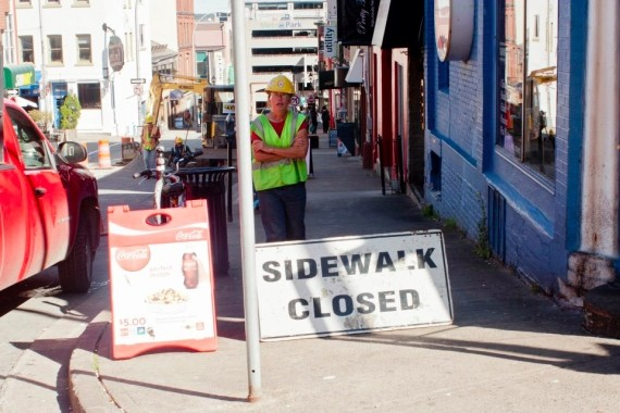 A construction worker blocks the sidewalk to Blowers Street businesses - STOO METZ
