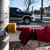 A gloved hand pushes a crosswalk button.