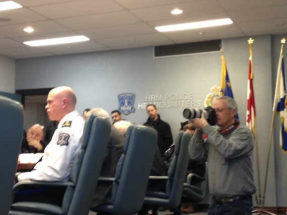 A media photographer takes a picture of the back of police chief Jean-Michel Blais' head.