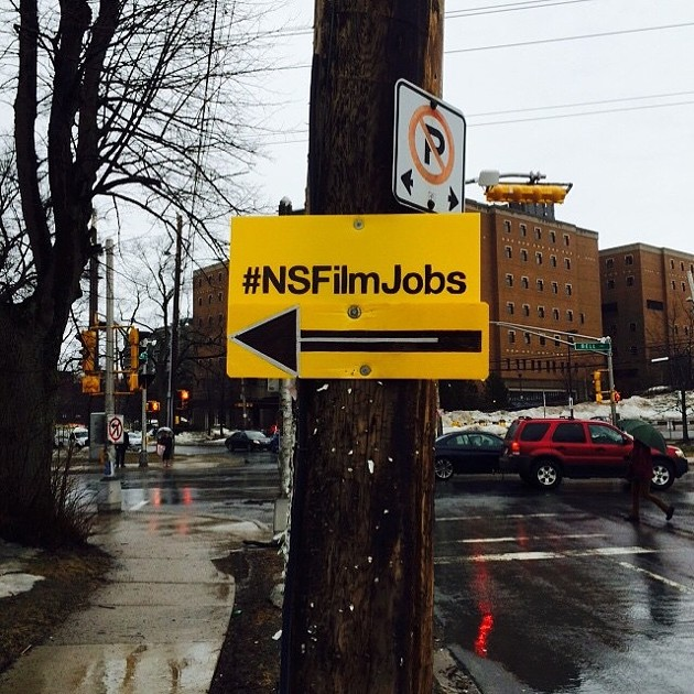 A sign with #NSFilmJobs attached to a telephone pole with an arrow pointing to the left.
