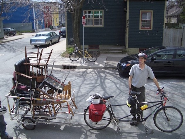 A staff member moving furniture by bicycle during the Ecology Action Centre renovation in 2006. - VIA EAC