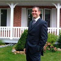 Aaron MacKenzie, a part-time teacher and full-time believer in trickle-up economics, stands in a suit in front of his house.