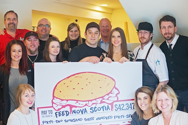 At The Coast office, several people gather around a giant cheque made out to Feed Nova Scotia.