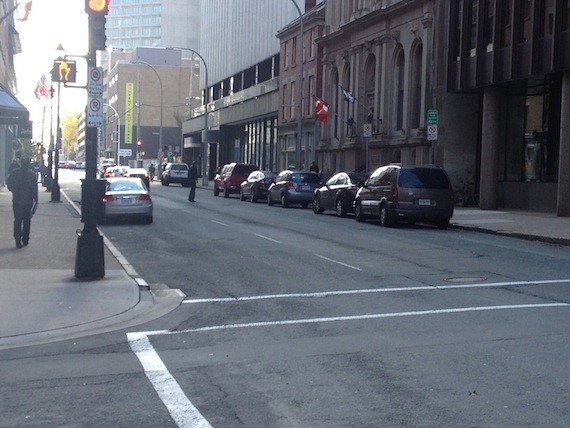 Bicyclists have a tight squeeze between parking on both sides of narrow Hollis Street.