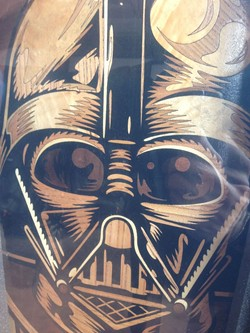 Darth Vader's face made out of wood inlay on the bottom of a skateboard.