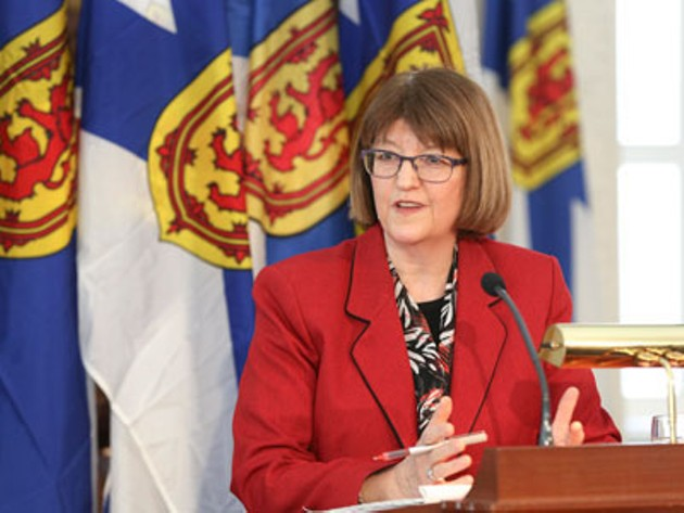 Diana Whalen at a press conference—she is standing at a podium, behind her are several Nova Scotia flags.