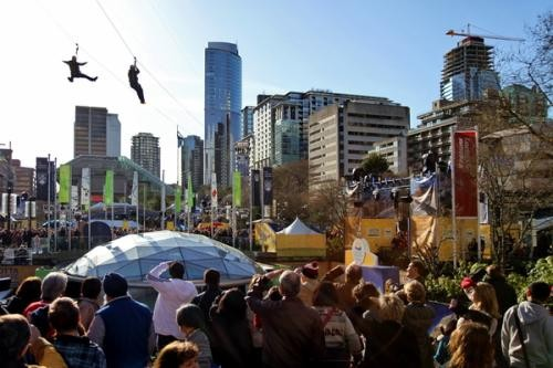 Olympics Day 3, Robson Square: 15 degrees Celsius.  Dozens salute the bravery of freestyle zip liners.