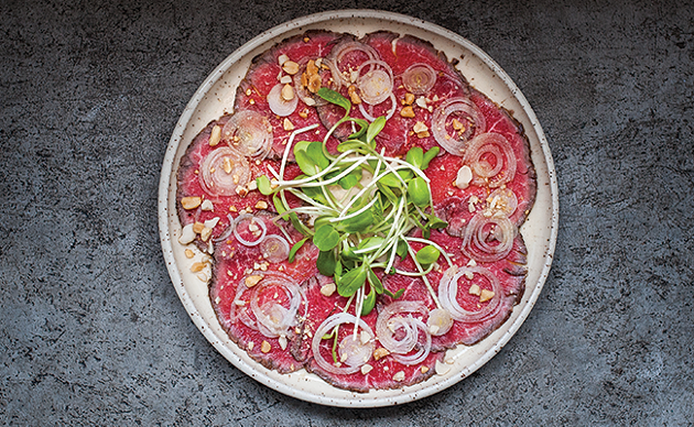 Beef tenderloin carpaccio with oishi, vinegar and chillies, sunflower shoots, peanuts and onion - JESSICA EMIN