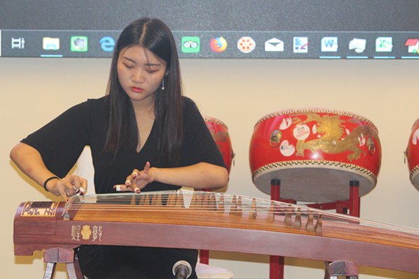 """Linshan Sui performs a traditional Chinese instrumental solo, """"The Spring in Lhasa,"""" on her guzheng, known in English as a zither, at the August 22 press conference. - JAMES LATTER"""