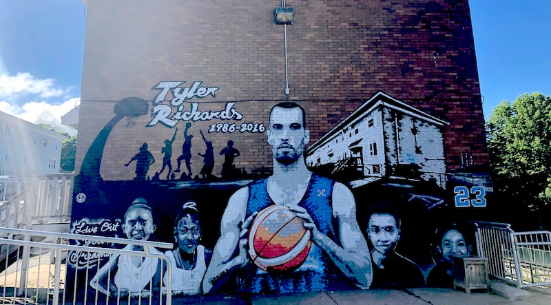 In the mural painted in his honour, Tyler Richards looks out over his community with a pensive, protective glare.