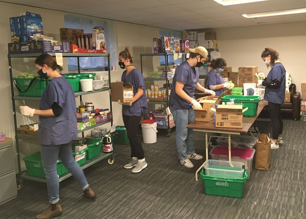 At the DSU food bank, volunteers prepare boxes for pick-up. - THE COAST