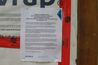 An eviction notice from the city pinned to the door of a temporary shelter. - THE COAST