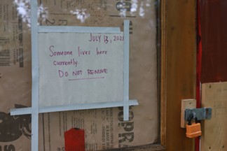 A sign on the door of a shelter tells police it is occupied and not to remove it. - THE COAST
