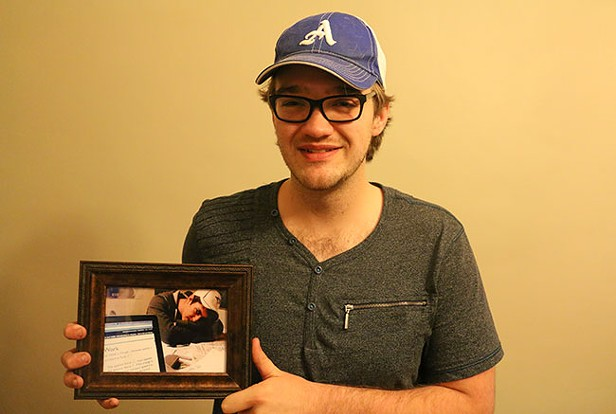 Thomas McCrossin, holding a picture of his best friend Taylor Samson, who's up late studying. - KIERAN LEAVITT