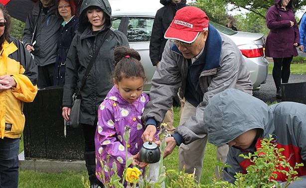 George Lee Sr. pours some hot tea over his wife's grave. - JENNIFER LEE