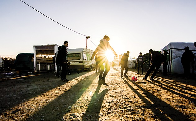 A group of Syrian refugees playing football with charity workers in Calais, France. - VIA ISTOCK