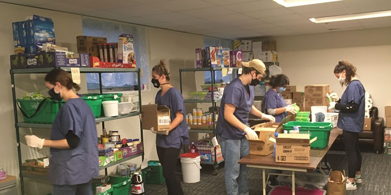 At the DSU food bank, volunteers prepare boxes for pick-up.