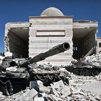 Two destroyed tanks in front of a mosque in Azaz, Syria, the site of a 2012 battle in the ongoing Syrian civil war.