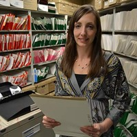 Melissa Mosher stands in front of the many files at the Residential Tenancies office in Halifax.