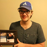 Thomas McCrossin, holding a picture of his best friend Taylor Samson, who's up late studying.