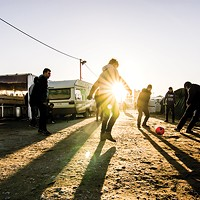 A group of Syrian refugees playing football with charity workers in Calais, France.