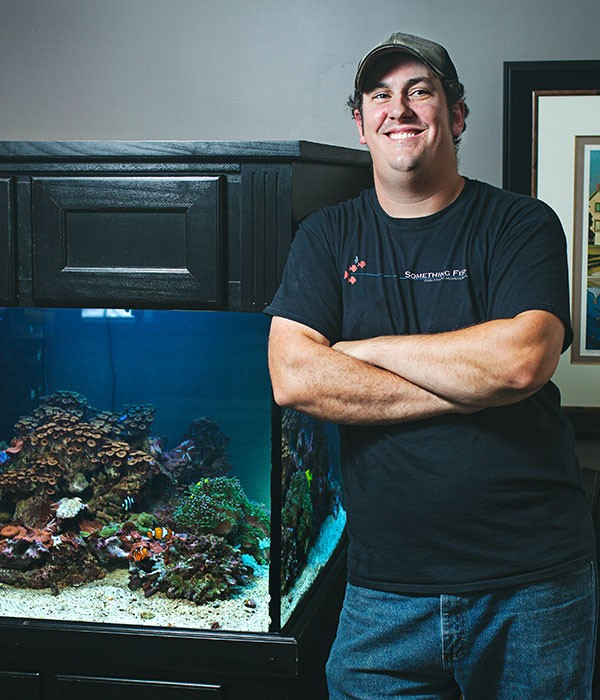 Cleaning fish tanks is a line of work Justin Wheeler just kind of fell into. - LENNY MULLINS