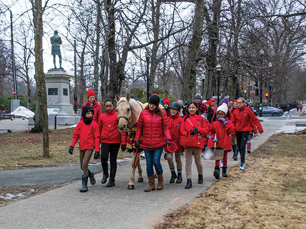 Angie Holt with a gaggle of Lancers walking Ben the pony to Ronald McDonald House. - SUBMITTED