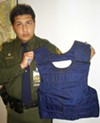 Border Patrol agent Mario Escalante holds a sophisticated bullet-proof vest found among garbage on Arizona's border.