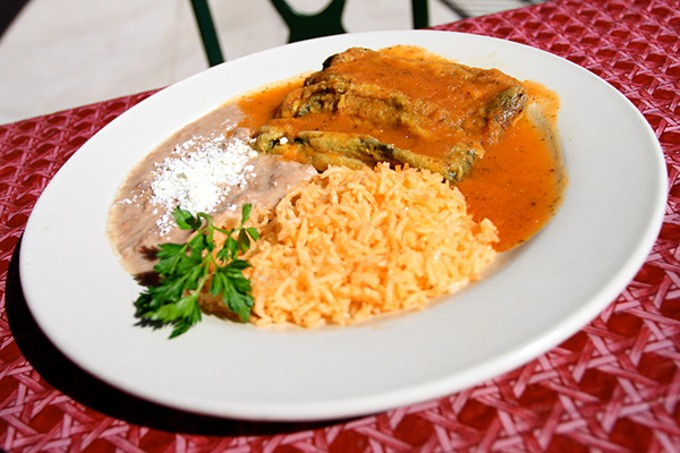 Chiles rellenos, one stuffed with ground beef and one stuffed with cheese.