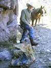 David Lowell stands outside a drug cave in Peck Canyon. The burlap bags at his feet have holes in them. They were discarded by burreros and replaced with new ones.