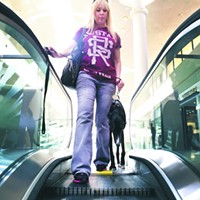 The Story of Mac & Jill Jill Macdonald steps onto an escalator with Mac at the Tucson Mall during a training session. After a few rides on the escalator, Mac became comfortable stepping on and off. Zachary Vito