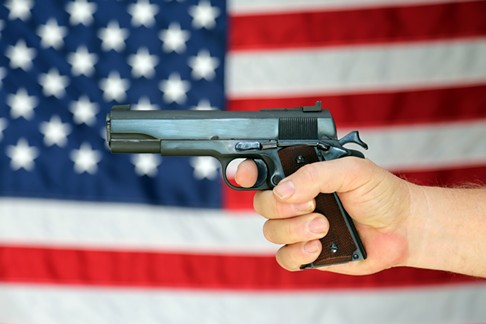 bigstock-a---pistol-is-held-in-front--111996575.jpg