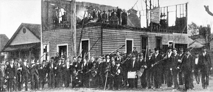 VIGILANTES OUTSIDE THE CHARRED REMAINS OF THE DAILY RECORD, COURTESY OF WIKIMEDIA.ORG