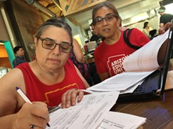 Tucson High School teachers Marea Janness (left) and Aida Castillo-Flores (right) sign up volunteers for petitioning sites at an INVESTinED gathering on June 6. - TORI TOM