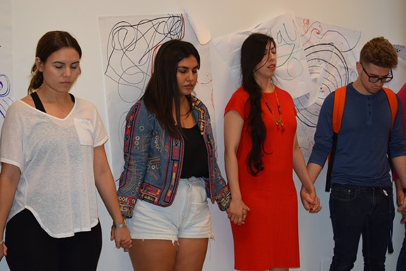 Niña Yhared (in red), a performance artist and researcher based in Mexico City, stands next to participants as they reflect on their art drawings depicting female migration during a workshop on Thursday, Oct. 11. - SAVANAH MODESITT