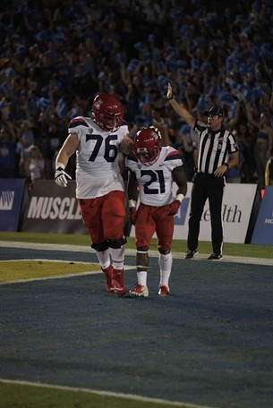 Offensive lineman Cody Creason, left, consoles running back JJ Taylor after he fumbled the football in the first half of Arizona's 31-30 loss to UCLA on Saturday night. - CONNOR BUSS, FOREWORD FILMS