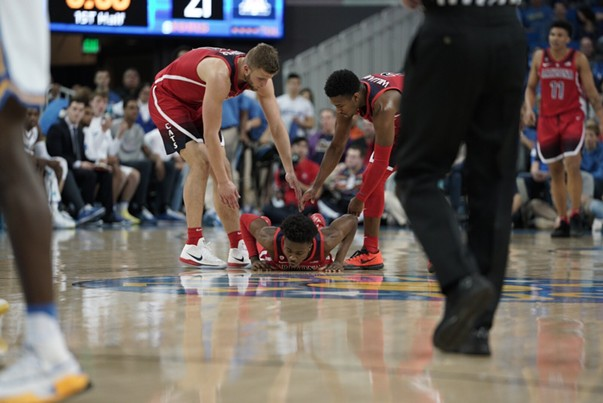 Arizona freshman Devonaire Doutrive gets some help up from his teammates during Arizona's 90-69 loss to UCLA on Saturday night. - CONNOR BUSS, FOREWORD FILMS