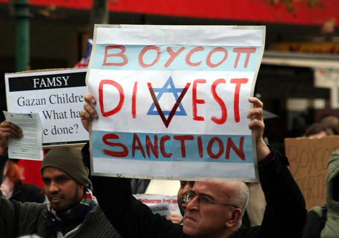 A protestor holds a sign in support of the Boycott Divest Sanction movement against the Israeli government. - WIKIMEDIA COMMONS