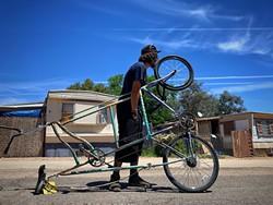 Adam fixing his bike. - BRIAN SMITH