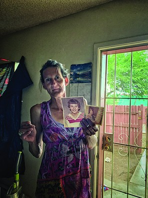 """Darlene holds photos of herself as a child. """"It was a long ago me. And it was yesterday."""" - BRIAN SMITH"""